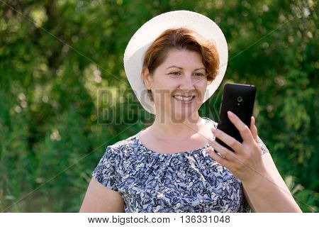 A woman in a hat looks at cell phone outside