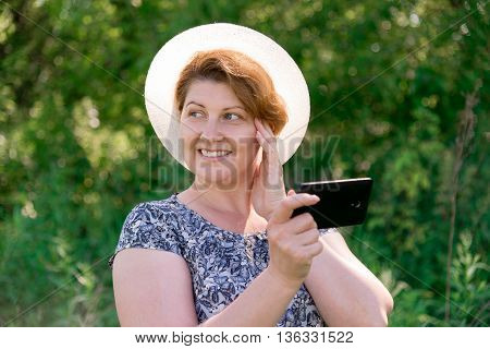 A woman in a hat with cell phone outside