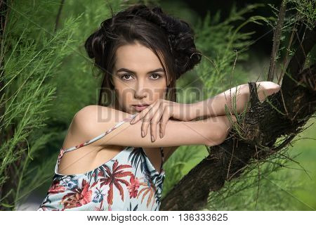 Sensuous girl in a flowered dress leans with her elbows on the tree on the background of trees. She holds her left hand on the right arm in front of her face and looks into the camera. Horizontal.