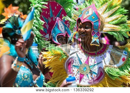 ATLANTA, GA - MAY 2016:  Women wearing elaborate feathered costumes walk in a parade to celebrate Caribbean culture along North Avenue in Atlanta GA on May 28 2016.