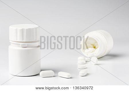 White plastic pill bottles and pills on white background