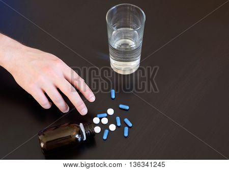 Hand On Table Taking A Pill With Water In The Glass