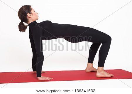 Beautiful athletic girl in black suit doing yoga. Purvottanasana asana plank pose. Isolated on white background.