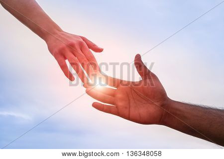 Black and white hand reaching - Handshake of different skin color hands united against racism and racial problems - Concept of human aid to migrant and refugees - Sun halo filter and dramatic lights