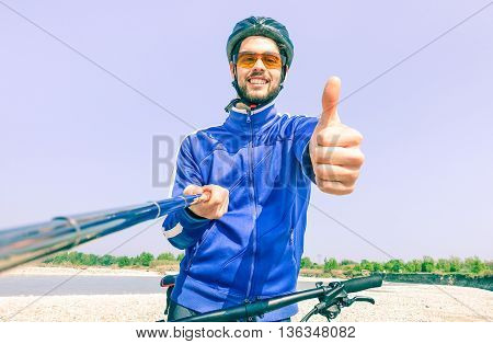 Young man with bike taking selfie outdoor by the river - Male self photo at bicycle excursion in a sunny summer day - Concept of freedom and healthy lifestyle using modern technology