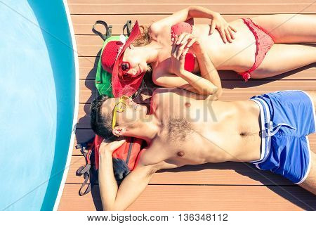 Young couple sun tanning at pool deck of cruise ship - Beautiful lovers holding hands lying on yacht poolside - Concept of unforgettable love moment on the honeymoon vacation - Soft vintage filter