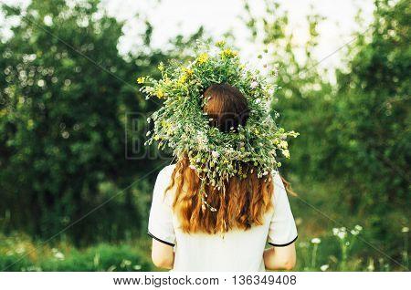 Beautiful Girl In Wreath Of Flowers  In Meadow On Sunny Day. Portrait Of Young Beautiful Woman Weari
