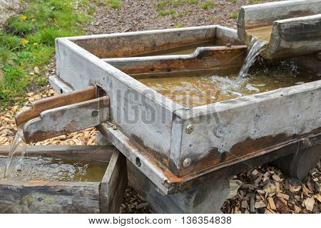 Stream of fresh Alpine water flowing through handmade wooden chute spout in Europe