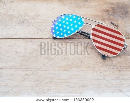 mirror glasses with american flag pattern on wooden background.4th of July concept.