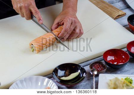 Hand holding knife cuts sushi. Thick sushi roll. Sushi chef cooks dinner. Proven recipe of japanese cuisine.