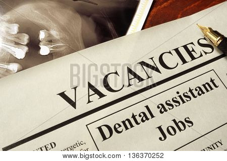 Newspaper with ads dental assistant jobs vacancy. Occupation concept.