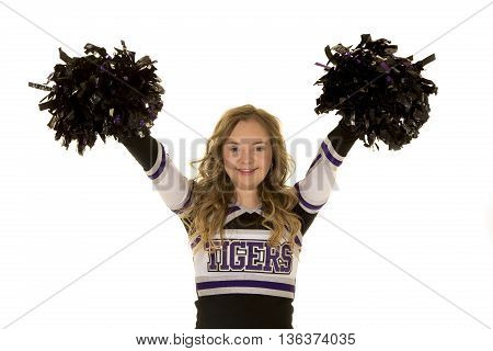 A cheerleader who has down syndrome with a big smile and her pom poms up in the air.