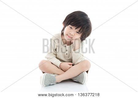 Portrait of unhappy Asian child sitting on white background isolated