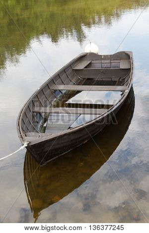 Rural wooden rowboat partly filled with water. No people