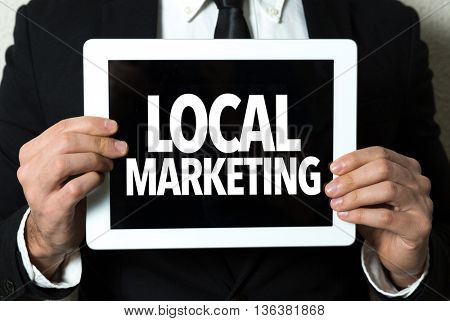 Business man holding a tablet with the text: Local Marketing