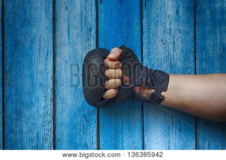One right-hand man in boxing gloves on a blue vintage background