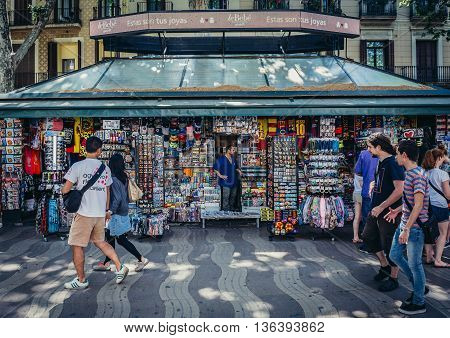 Barcelona Spain - May 26 2015. Tourists and city residents passes next to souvenirs shop at famous La Rambla street