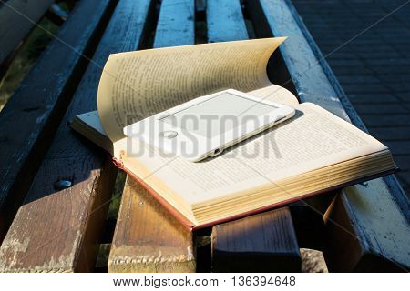 ebook laying on a book outdoor on the bench. new technology concept