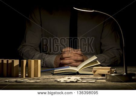 Concept person in contemplation or solving problems with folded hands near book and puzzle pieces under desk lamp.