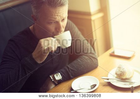 Attractive mid adult man drinking morning coffee in cafe, image toned