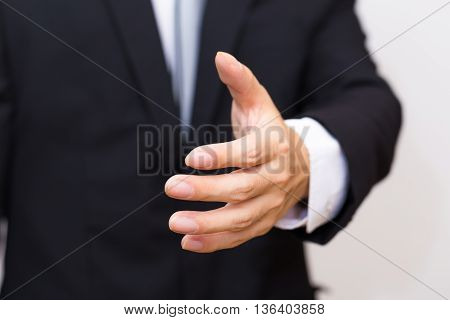 Businessman's Hand Sending For Shake Sign In Black Suit.