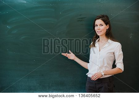 Woman pointing finger at blank board. School teacher pointing the finger at a blank board. Student stands at the blackboard. Business woman presenting the idea to the board. Girl in the school