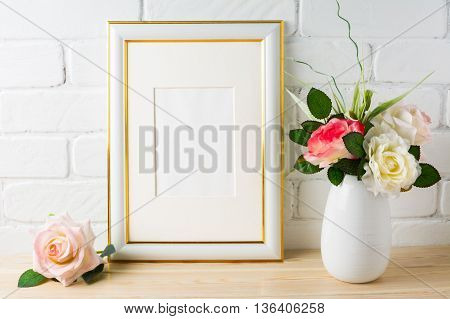 White frame mockup on brick wall with roses. Vertical white frame mockup for portrait or poster. Empty white frame mockup for design presentation.