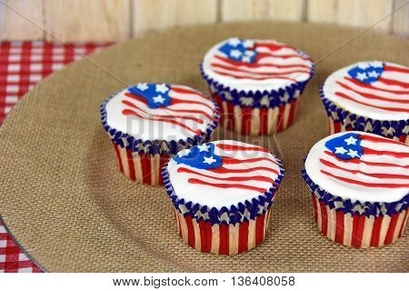 Patriotic American cupcakes with flag frosting on brown burlap plate.