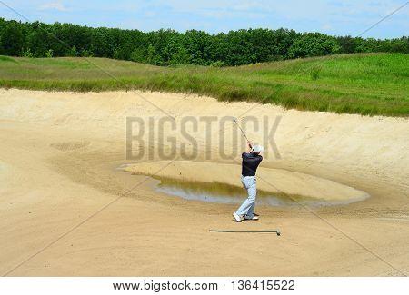 Golfer Hitting Ball with Club. Golfer on golf course.