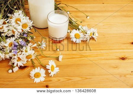 Simply stylish wooden kitchen with bottle of milk and glass on table, summer flowers camomile, healthy foog moring concept noone