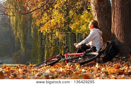 Young Woman Cyclist Relaxing On Sunny Autumn Outdoor