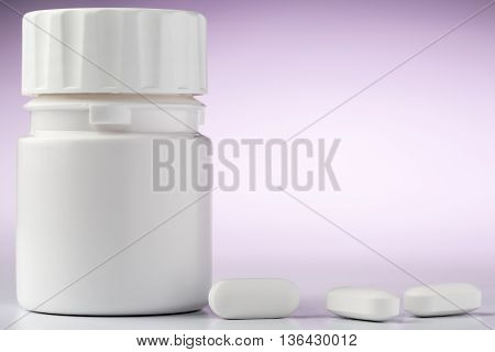 A bottle of aspirin pills and three pills in the foreground.Close-up on pink background
