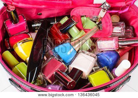 Set of nail polish mascara nail clippers in a pink purse.