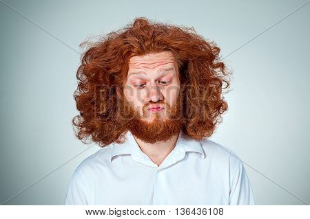 The portrait of disgusted man with long red hair