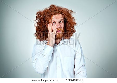 The young discouraged man with long red hair looking at camera