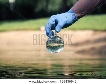 Water sample. Hand in glove holding a retort with clear water. Concept - water purity analysis environment ecology. Water testing for infections permission to swim