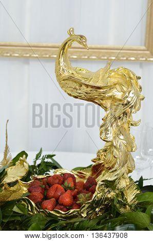 Golden bird  peacock statue. Strawberries in gold plate.