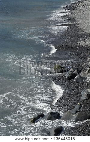 Waves from Atlantic Ocean breading on beach of volcanic rock in Madeira Portugal