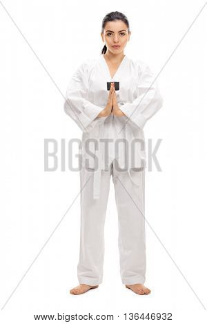 Full length portrait of a female martial artist bowing towards the camera isolated on white background