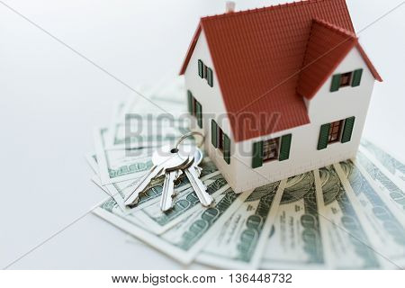 mortgage, investment, real estate and property concept - close up of home model, dollar money and house keys