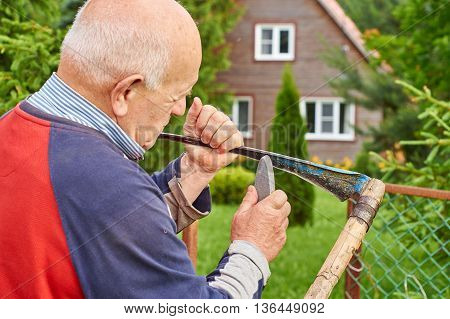 Elderly strong man sharpening a scythe before mowing the grass in front of his summer residence