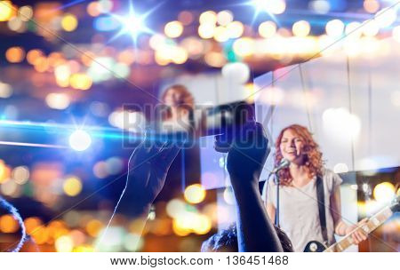 nightlife, music, technology and people concept - close up of singer playing electric guitar and singing on stage over fans crowd taking picture or video by tablet pc computer at concert in night club