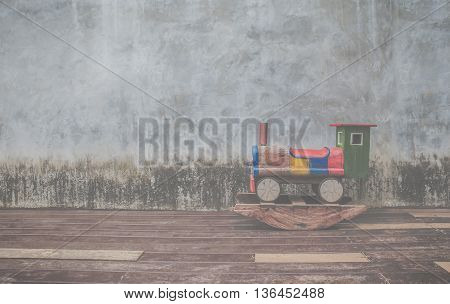 Wooden toy train on old cement background.Vintage filter.