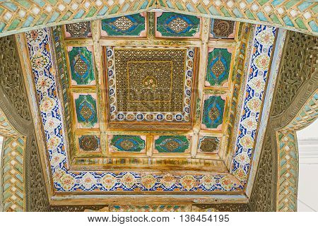 BUKHARA UZBEKISTAN - APRIL 29 2015: The carved ceiling of the porch at harem entrance of Sitorai Mokhi-Khosa Palace overlooks the pool on April 29 in Bukhara.