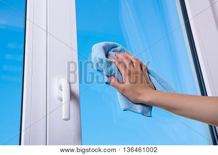 Woman's Hand Cleaning Window With Special Rag