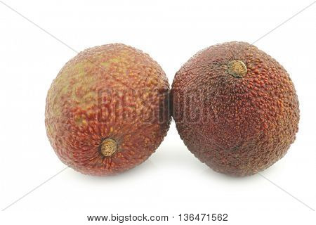 two fresh eat ripe avocado's on a white background