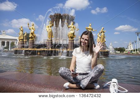 Young beautiful woman has a rest sitting near the Fountain of friendship of the people daily view at VDNH exhibition in Moscow, Russia