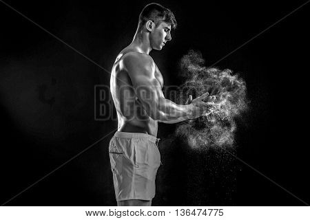young muscular man preparing to hand lifting heavy weight. White talcum dynamically scatters in different directions. Black and white
