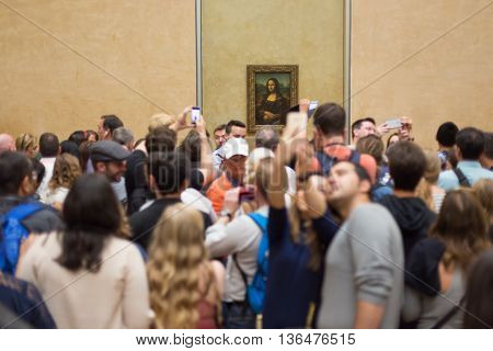 Paris, France - June 12: Crowd of visitors takes photos of Leonardo DaVinci's Mona Lisa, one of world's most famous work of art, at Louvre Museum on 12th of June , 2016 in Paris, France.