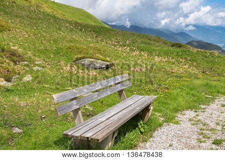 Wooden bench provided for hikers to rest while hiking at Zillertal Alps surrounded by mountains during summer in Tyrol, Austria, Europe